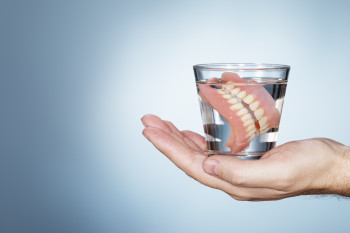 Man holding a glass containing dentures.